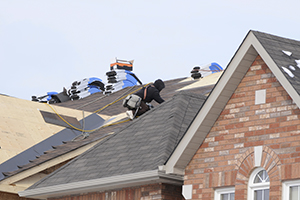 A roofer shingling a roof.